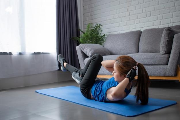 Jonge aziatische vrouw is ze blij om te oefenen in het huis. workout thuis.