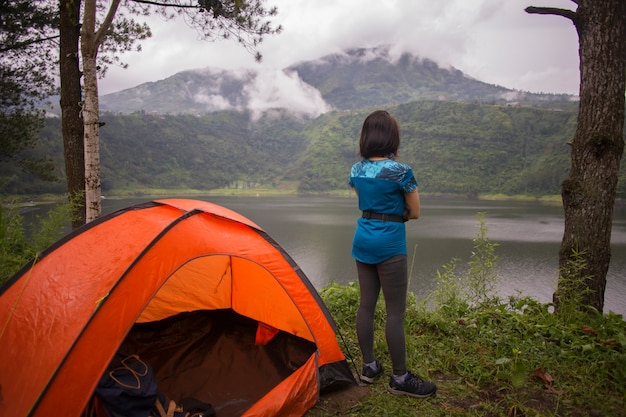Jonge aziatische vrouw kamperen of picknick in bosmeer.