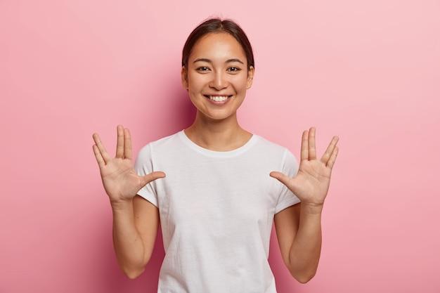 Jonge aziatische vrouw maakt vulkaangroet handgebaar, houdt armen omhoog en handpalmen naar voren met uitgestrekte duimen, middelvinger en ringvinger uit elkaar, begroet je, zegt: leef lang en voorspoedig. lichaamstaal