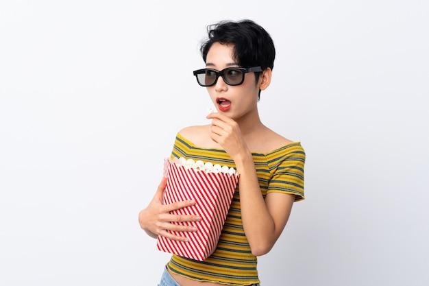 Jonge aziatische vrouw met 3d glazen en het houden van een grote emmer popcorns terwijl het kijken kant