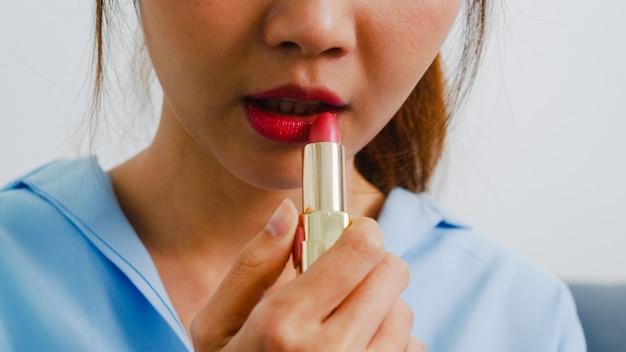 Jonge aziatische vrouw met behulp van lippenstift make-up voor spiegel, gelukkig wijfje die schoonheidsschoonheidsmiddelen gebruiken om zich klaar te verbeteren om in slaapkamer thuis te werken