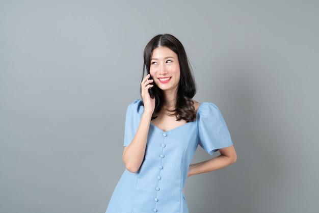 Jonge aziatische vrouw met behulp van mobiele telefoon met blij gezicht in blauwe jurk op grijs