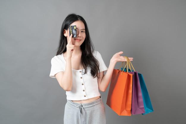 Jonge aziatische vrouw met behulp van telefoon met hand met boodschappentas op grijze ondergrond