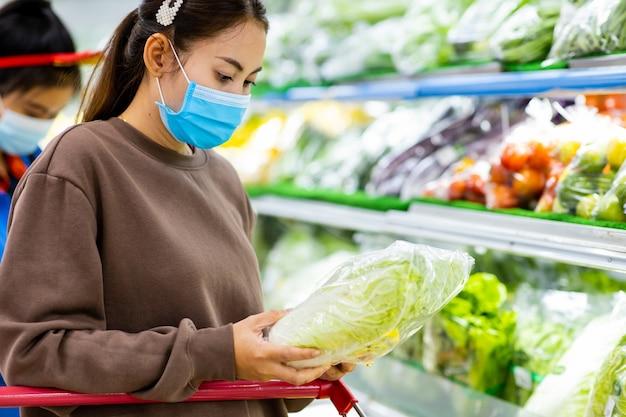 Jonge aziatische vrouw met beschermend masker duwen winkelwagentje voor het kopen van verse groenten in de supermarkt tijdens de uitbraak van het virus covid-19. concept ter preventie van covid-19 virus.