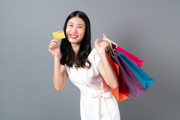 Jonge aziatische vrouw met blij gezicht en hand met boodschappentassen en creditcard op grijze muur