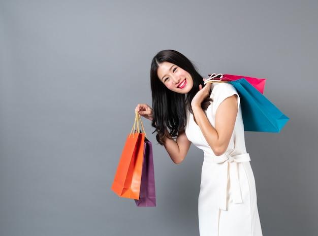 Jonge aziatische vrouw met blij gezicht en hand met boodschappentassen op grijs