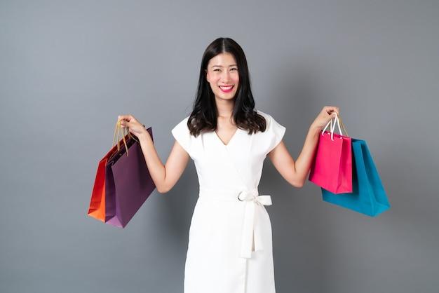 Jonge aziatische vrouw met blij gezicht en hand met boodschappentassen op grijze achtergrond