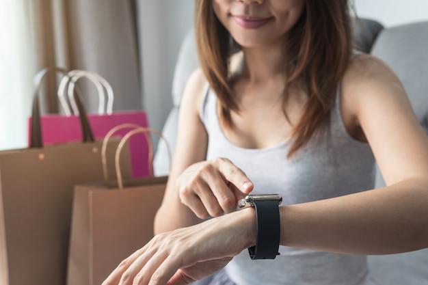 Jonge aziatische vrouw met boodschappentas met behulp van slimme horloge thuis
