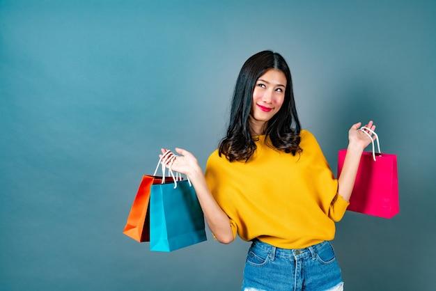 Jonge aziatische vrouw met boodschappentassen in geel shirt op blauw
