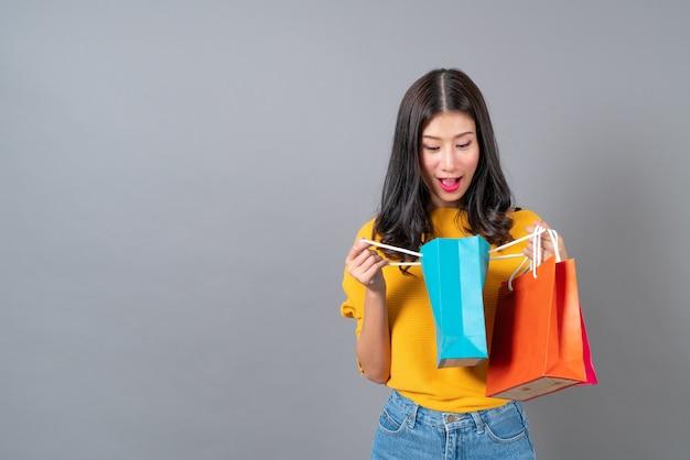 Jonge aziatische vrouw met boodschappentassen in geel shirt op grijs