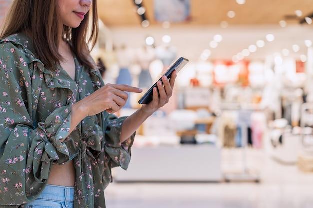 Jonge aziatische vrouw met boodschappentassen met behulp van slimme telefoon en winkelen in winkelcentrum, woman lifestyle concept