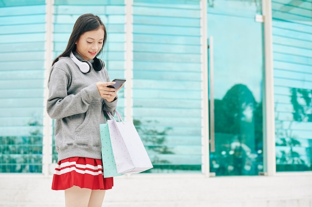 Jonge aziatische vrouw met boodschappentassen permanent buiten en het controleren van meldingen in haar smartphone