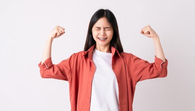 Jonge aziatische vrouw met bretels op tanden in brede glimlach en heft wapens op en toont sterk krachtig.