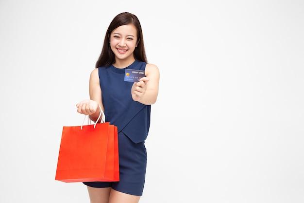 Jonge aziatische vrouw met creditcard en rode boodschappentassen geïsoleerd op een witte muur
