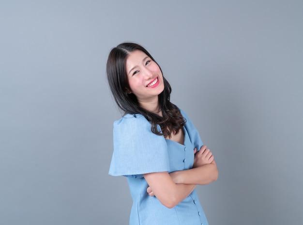 Jonge aziatische vrouw met een blij en lachend gezicht in blauwe jurk