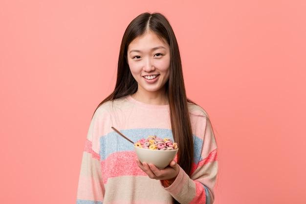 Jonge aziatische vrouw met een gelukkig, glimlachende en vrolijke graangewassenkom.