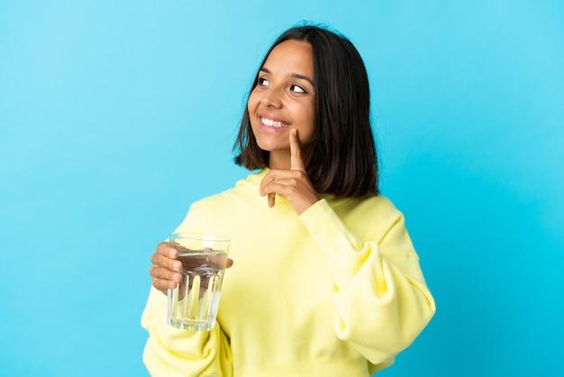 Jonge aziatische vrouw met een glas water dat op blauwe muur wordt geïsoleerd die een idee denkt terwijl het omhoog kijken
