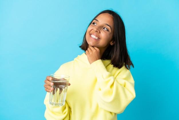 Jonge aziatische vrouw met een glas water dat op blauwe muur wordt geïsoleerd die tijdens het glimlachen omhoog kijkt