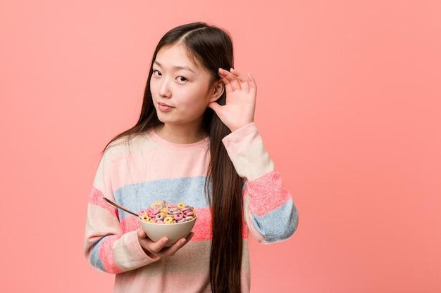 Jonge aziatische vrouw met een graangewassenkom die aan een roddel probeert te luisteren.