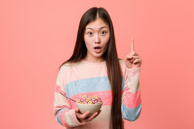 Jonge aziatische vrouw met een graangewassenkom die één of ander groot idee, concept creativiteit hebben.