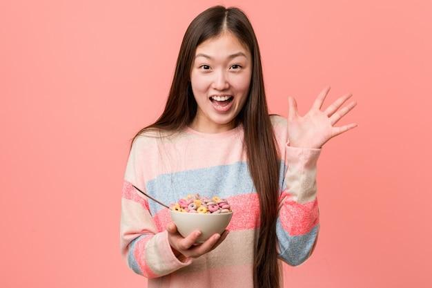 Jonge aziatische vrouw met een graangewassenkom die een overwinning of een succes viert