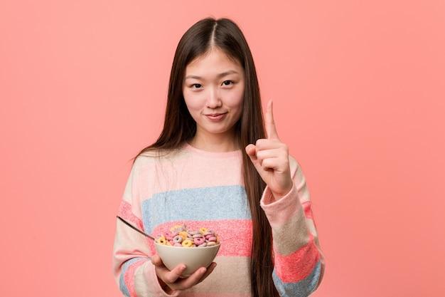 Jonge aziatische vrouw met een graangewassenkom die nummer één met vinger tonen.