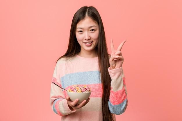 Jonge aziatische vrouw met een graangewassenkom die nummer twee met vingers tonen