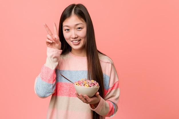 Jonge aziatische vrouw met een graangewassenkom die overwinningsteken tonen en breed glimlachen.