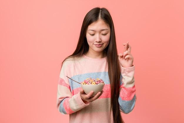 Jonge aziatische vrouw met een graangewassenkom die vingers kruisen voor het hebben van geluk