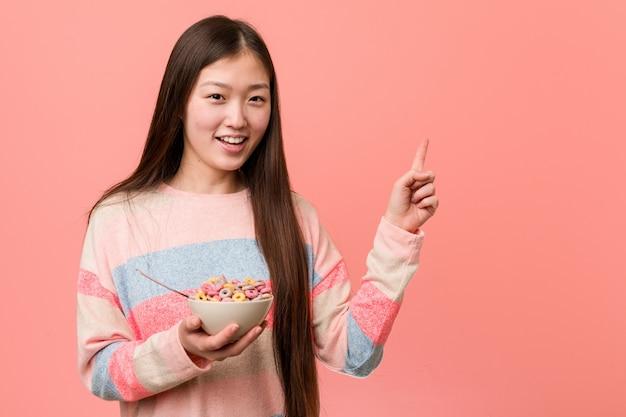 Jonge aziatische vrouw met een graangewassenkom die vrolijk het richten met weg wijsvinger glimlachen.