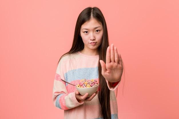 Jonge aziatische vrouw met een graangewassenkom die zich met uitgestrekte hand bevinden die eindeteken tonen, die u verhinderen.