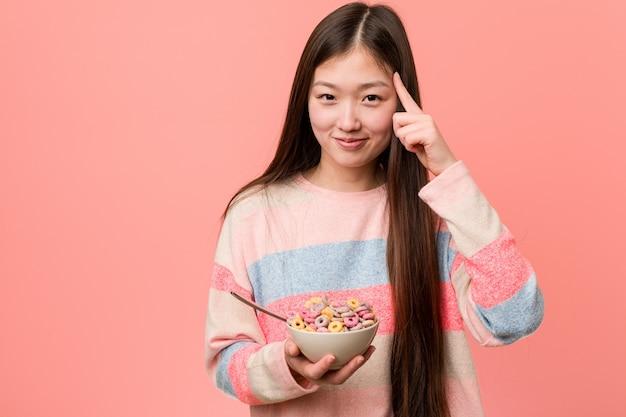 Jonge aziatische vrouw met een graangewassenkom die zijn tempel met vinger richten, denken, geconcentreerd op een taak.