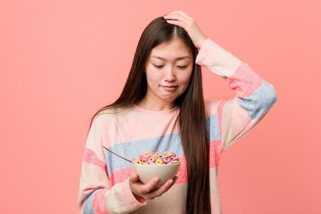 Jonge aziatische vrouw met een graankom die wordt geschokt, heeft zij belangrijke vergadering herinnerd.