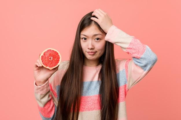 Jonge aziatische vrouw met een grapefruit die wordt geschokt, heeft zij belangrijke vergadering herinnerd.