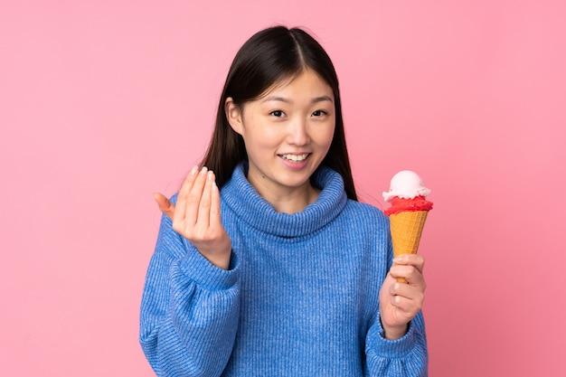 Jonge aziatische vrouw met een ijsje op roze muur die met hand uitnodigt te komen