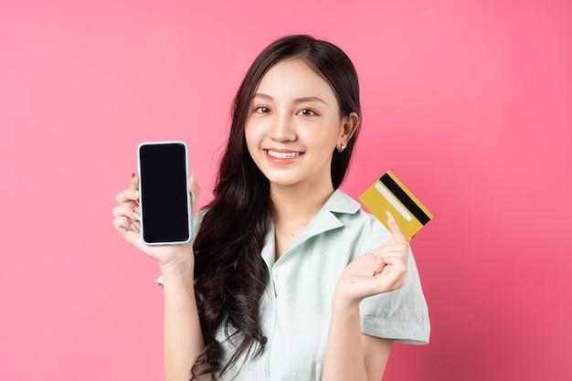 Jonge aziatische vrouw met een mobiele telefoon terwijl ze een bankkaart in haar hand op roze houdt