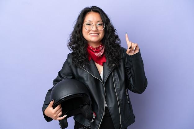 Jonge aziatische vrouw met een motorhelm geïsoleerd op een paarse achtergrond die een vinger toont en opheft in teken van de beste