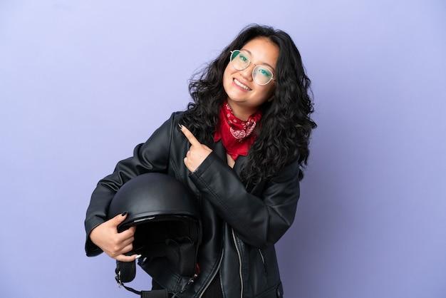 Jonge aziatische vrouw met een motorhelm geïsoleerd op een paarse achtergrond die naar de zijkant wijst om een product te presenteren
