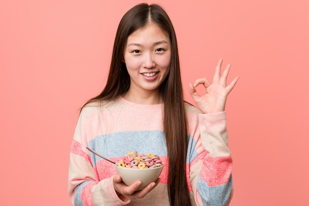 Jonge aziatische vrouw met een vrolijke en zekere tonende kom die van het graangewas ok gebaar toont.