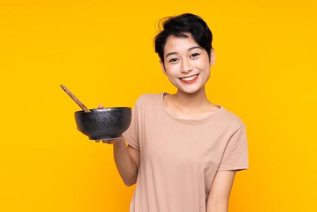 Jonge aziatische vrouw met gelukkige uitdrukking terwijl het houden van een kom van noedels met eetstokjes