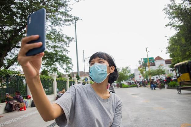 Jonge aziatische vrouw met gezichtsmasker die mobiele telefoon selfie in openbare ruimtes gebruiktcorona virusconcept