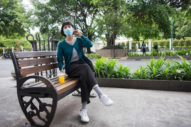 Jonge aziatische vrouw met gezichtsmasker zittend in openbare ruimtes corona virus concept