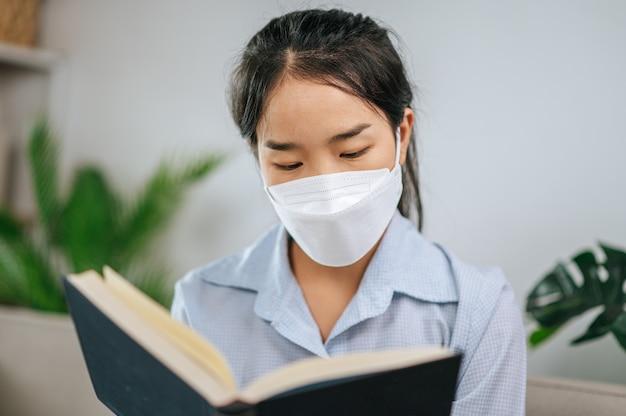 Jonge aziatische vrouw met gezichtsmasker zittend op de bank in de woonkamer, ze leest boek tijdens quarantaine covid-19 zelfisolatie thuis