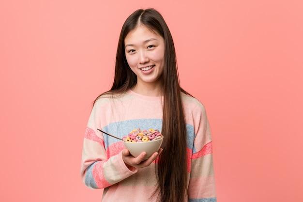 Jonge aziatische vrouw met graangewassenkom glimlachen zeker met gekruiste wapens.