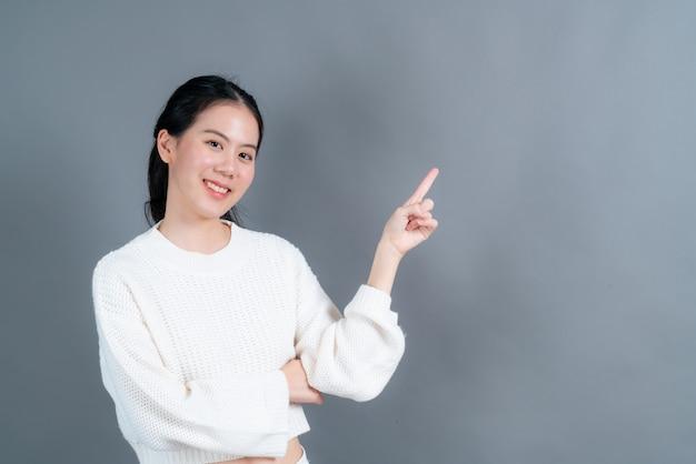 Jonge aziatische vrouw met hand die aan kant voorstelt