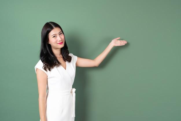 Jonge aziatische vrouw met het glimlachen gezicht en hand die aan kant in groen voorstellen