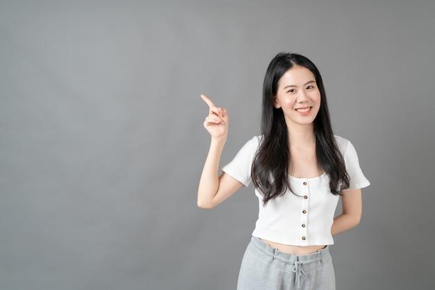 Jonge aziatische vrouw met het glimlachen gezicht en hand die op exemplaarruimte richten
