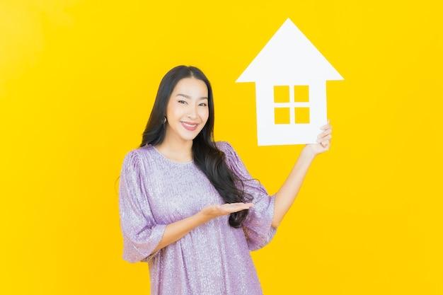 Jonge aziatische vrouw met huis- of huispapierteken op geel