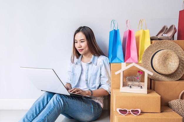 Jonge aziatische vrouw met kleurrijke boodschappentas en stapel kartonnen dozen