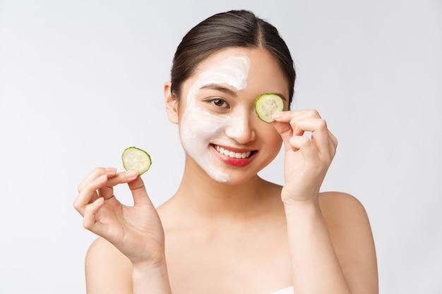Jonge aziatische vrouw met komkommer op haar ogen